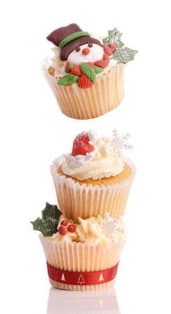 Christmas cupcake tower with top cake decorated with a snowman, all on white background photo