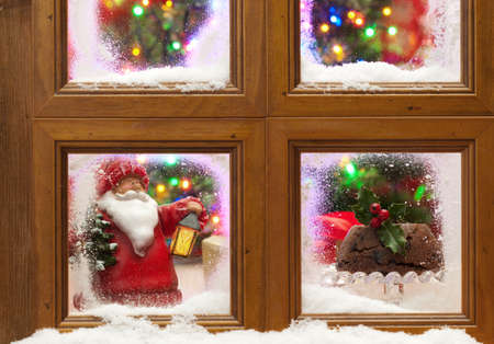 Snowy window with Christmas pudding and tree with twinkling fairy lights Stock Photo