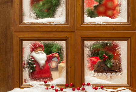 Festive Christmas frosty window with figgy pudding and father Xmas ornament, focus on Christmas pudding photo