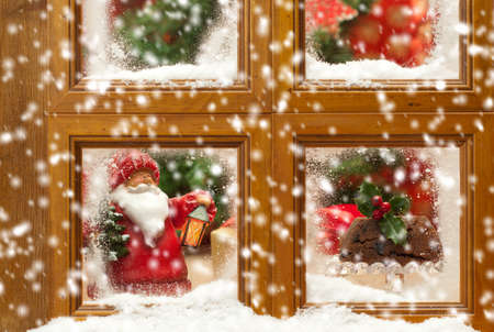 Falling snow against a festive Christmas frosty window scene photo
