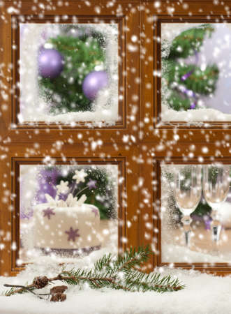 Falling winter snow onto pine cones and branch against a festive Christmas window, focus on pine cones and branch in front of window photo