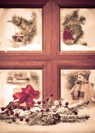 Vintage Christmas window with snowy scene, focus on fir cone and branch in front of window