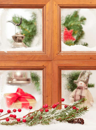 Looking into a festive Christmas window with branch covered in snow photo