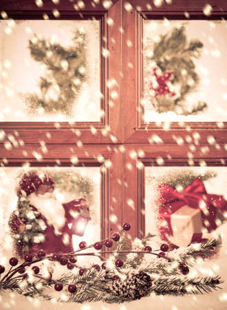 bow window: Looking into a festive seasonal Christmas window as snow falls outside