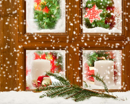 Candles at a festive seasonal window as snow falls onto a pine branch outside Stock Photo - 11713593