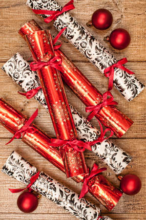 crackers: Homemade Christmas crackers on wooden background with red baubles