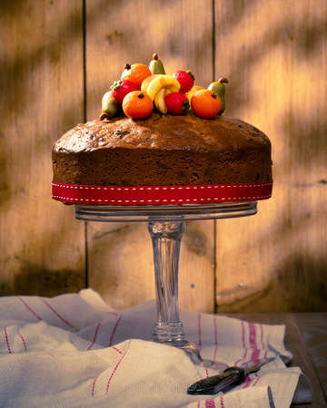 Rich fruit cake decorated with marzipan fruits with vintage feeling photo