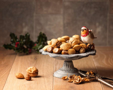 cobnut: Mixed nuts in dish with nut crackers and holly in background Stock Photo