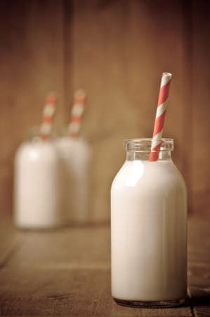 further: Retro milk bottle with striped drinking straw and further bottles in background Stock Photo