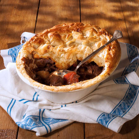 Game pie in serving dish on rustic background with spoon Standard-Bild