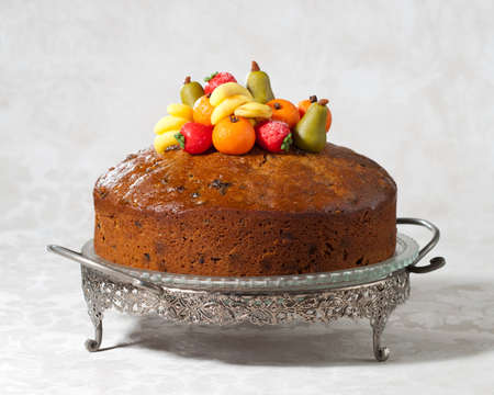 cakestand: Luxury rich fruit cake on cakestand decorated with traditional marzipan fruits