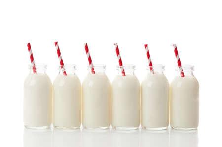 vaso de leche: Fila de botellas llenas de leche de vidrio con pajitas para beber retro rojo y blanco sobre un fondo blanco