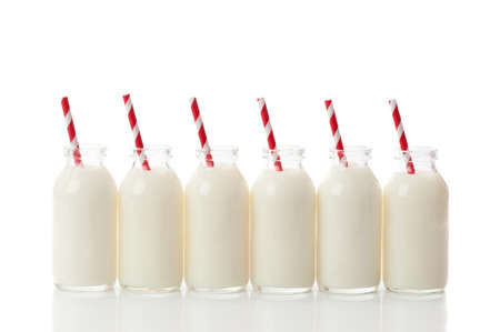 Row of filled glass milk bottles with retro red and white drinking straws on a white background