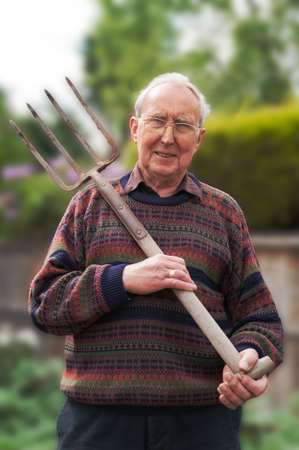 Senior citizen male with garden fork in his garden photo