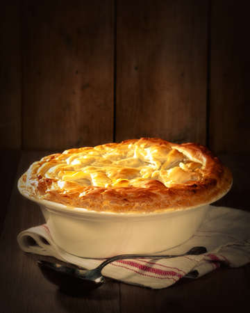 meat pie: Game pie in serving dish on rustic background with spoon Stock Photo
