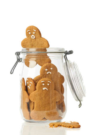 Gingerbread man escaping the jar of cookies on white background photo