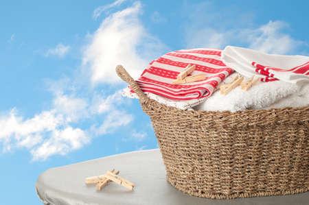 Cesta de toallas recién lavadas sobre tabla de planchar contra un cielo azul del verano Foto de archivo