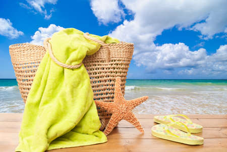 Beach items for a day at the seaside with basket, towel and flip flops on decking against a summer beach
