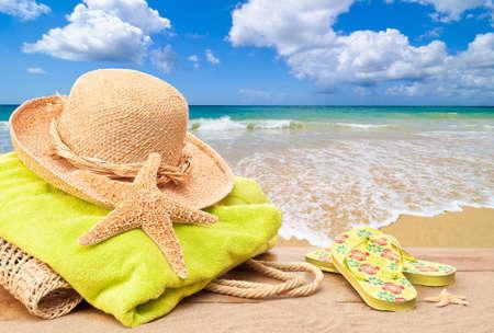 Sac de plage avec une serviette et chapeau de soleil donnant sur l'océan Banque d'images