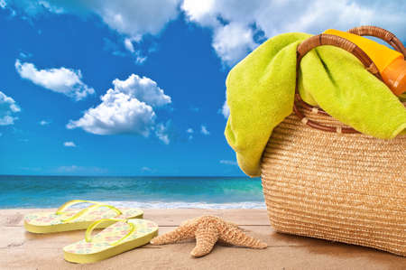 estrella de mar: Bolsa de playa con una toalla y protector solar con vistas al mar Foto de archivo