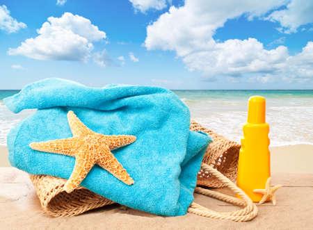 Vacaciones en la playa canasta con toalla y protector solar con vistas a una idílica playa de arena Foto de archivo