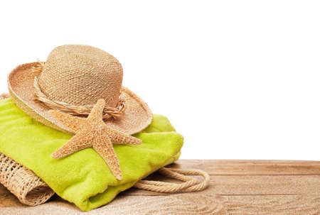 sunhat: Beach bag and towel on sandy decking with white copyspace