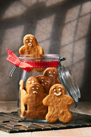 gingerbread man: Gingerbread man climbing out of the cookie jar Stock Photo