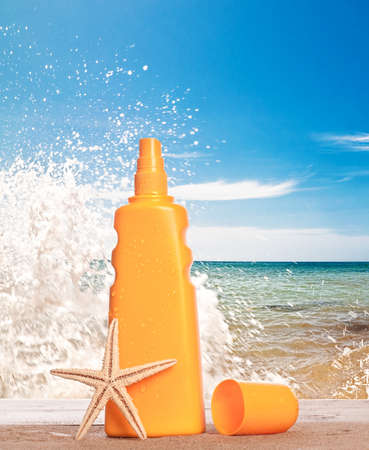 Suntan lotion bottle against beach background with sea splash photo