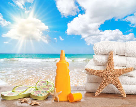 Sunscreen lotion with towels and flip flops overlooking the ocean photo