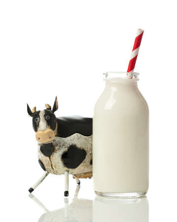 Fresh milk in retro glass bottle with drinking straw on a white background photo