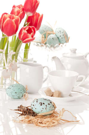 Easter tea setting with tulips and Easter eggs on white background photo