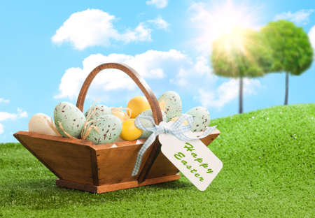 Easter eggs in wooden trug in springtime setting photo
