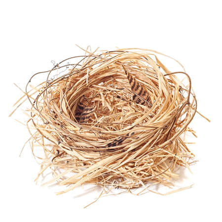 Empty straw nest with twigs and feathers on a white background