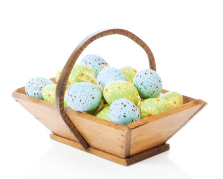 speckled wood: Collection of Easter eggs in wooden trug on a white background
