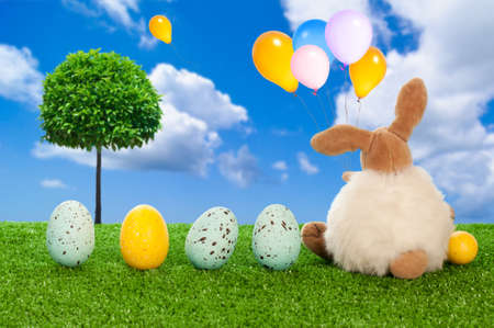 Easter eggs and the Easter bunny holding colorful balloons photo