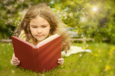 learning to read: Girl reading book in summer field