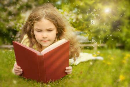 Girl reading book in summer field