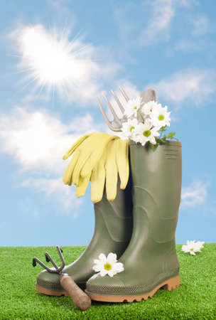 Wellington boots with garden tools on grass with blue summer sky photo
