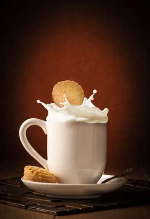 Cookie with milk splash in mug on a dark background Stock Photo - 12463896