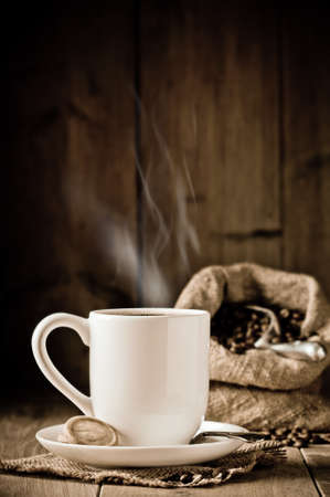 Cup of steaming coffee with biscuits - sack of coffee beans in background