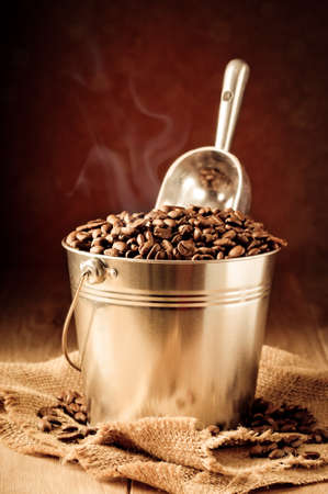 Bucket and scoop of coffee beans on burlap sack photo