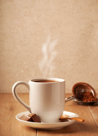 Mug of steaming hot chocolate with cocoa powder in background