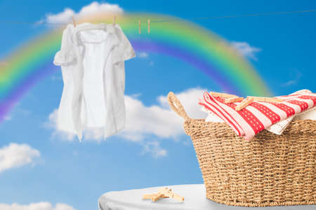 clothes pegs: Basket of fresh laundry against blue sky with rainbow Stock Photo