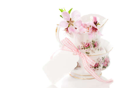 Pretty vintage china with spring blossom and blank label tied with ribbon - copy space provided photo
