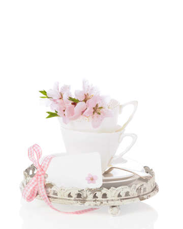 Teacups filled with spring flowers with blank greeting card on white background photo