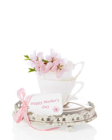 White china teacups filled with spring blossom with Mother's Day greeting on white background