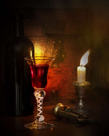 Candle lit scene with vintage port in antique glass photo