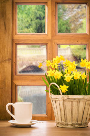 Spring window with bucket of daffodil flowers with rain falling outside