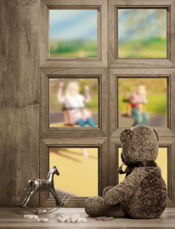 left behind: Teddy bear watches from the nursery window - waiting for the return of the children playing on the swings