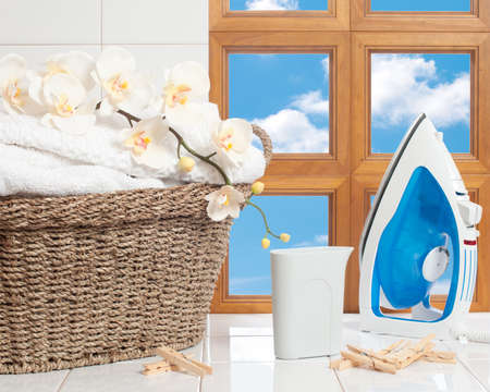 clothes pegs: Housework concept with fresh laundry and iron against a window with blue sky Stock Photo